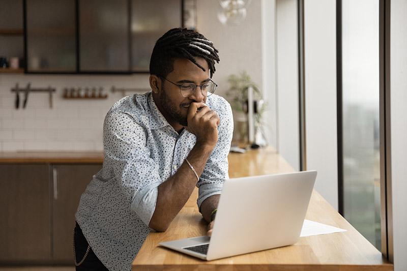 Man looking at computer thinking